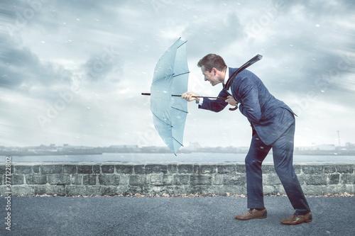 Carta da parati Businessman with an umbrella is facing strong headwind