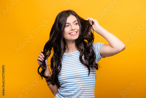 Vászonkép brunette woman toughing curly long hair and smiling isolated on yellow