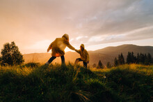 Two Hikers In Yellow Jackets Climb To The Top Of The Mountain Holding Hands In The Rain. A Man Helps A Friend To Raise His Hand To The Top Against The Backdrop Of A Mountain Landscape At Sunset.