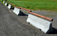 Concrete Roadblock Used On The Highway Between Two Lanes And Driving Directions Connected By Wooden Poles In The Shape Of A Mobile Railing That Will Not Allow Cars To Park In The Meadow Low Fence