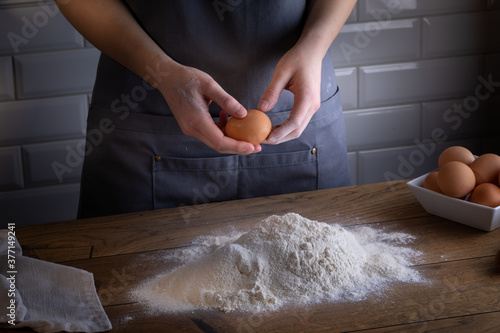 Fototapety, obrazy: Breaking eggs by chefs hands during cooking dough for dumplings, pasta, bread, or pizza.  Cooking dumplings – step by step guide.