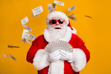 Portrait Of His He Nice Attractive Cheerful Glad Lucky Fat Overweight Bearded Santa Holding In Hand Throwing Usd 100 Cash Interest Rate Loan Isolated Bright Vivid Shine Vibrant Yellow Color Background