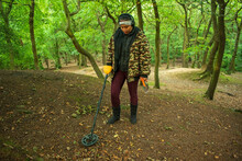 Asian Female Metal Detecting In Woodland Forest