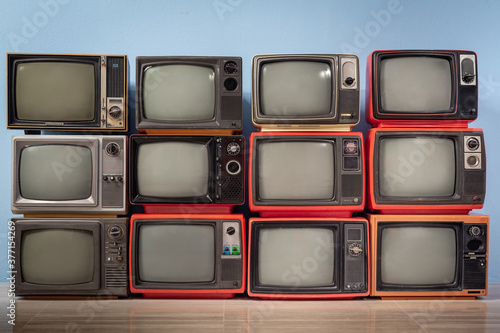 Old vintage televisions pile in the room. TVs wall,  background Fototapet
