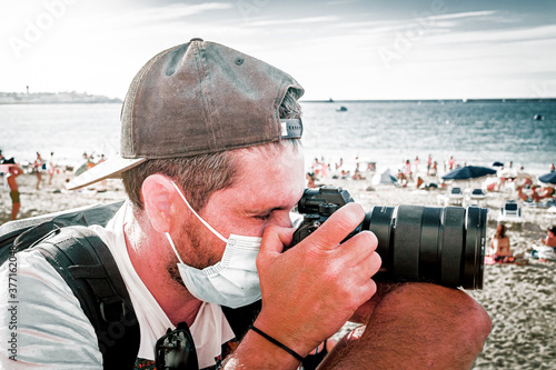 Papel de parede male photographer taking photos on the beach with mask in period of covid 19