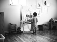 Black And White Photo Of Boy Drawing At Easel