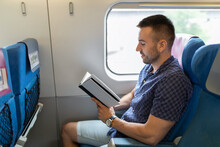 Man Reading A Book At The Train