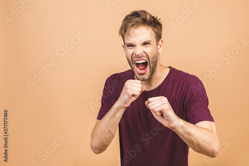 Fototapeta Furious, enraged man with grumpy grimace on his face,with mouth opened in shout, ready to argue and swear, wants to gain respect, show strength, isolated over beige background