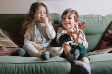 Young Cute Kids Playing With Mannequin On The Couch