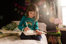 Girl Writes In Diary In Bedroom