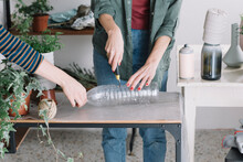 Woman Cutting Recycled Plastic Bottle To Diy A Vase