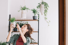 Smiling Woman Choosing Small Plant To Put In Diy Recycled Pot
