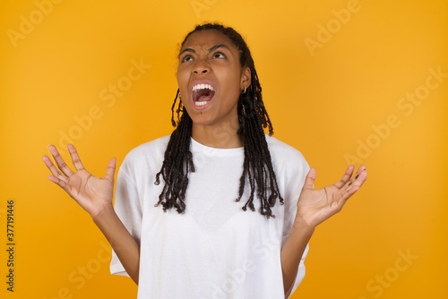 Fotografie, Tablou Young dark skinned woman with braids hair wearing white t-shirt over yellow background crazy and mad shouting and yelling with aggressive expression and arms raised