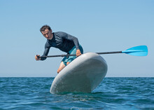 Man Surfing On Inflatable Stand-up Paddle Board At Summer Sunny Day. Extreme Sport Activity