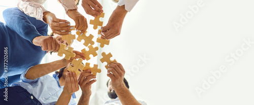 Canvas Print Happy company employees joining parts of jigsaw puzzle during work meeting or te