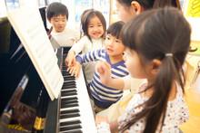 ピアノを弾く先生と歌う幼稚園児