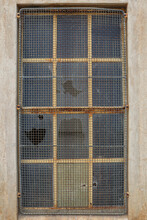 Broken Glass Window Panes And Rusty Metal Security Grille On A Concrete Structure