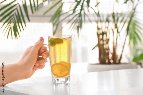 Fototapeta Woman drinking tasty cold ice tea at table obraz