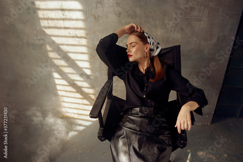 Fotografie, Obraz Stylish redhead sexy woman in black blouse, leather skirt and polka dot kerchief sitting at high chair in loft interior gainst gray concrete wall and smoke with sun beams