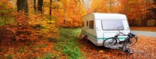 Caravan Trailer With A Bicycle Parked In A Golden Beech Tree Forest. Colorful Red, Orange And Yellow Leaves On The Ground. Panoramic Autumn Landscape. Leisure Activity In Heidelberg, Germany