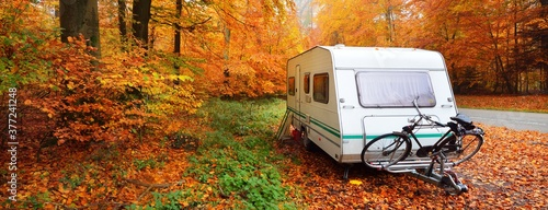 Caravan trailer with a bicycle parked in a golden beech tree forest Fotobehang