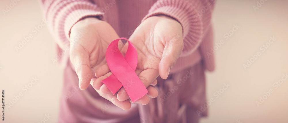 Fototapeta woman hands holding pink ribbon, breast cancer awareness, October pink, World cancer day concept