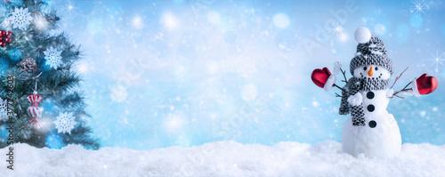Fotografie, Obraz Happy snowman with Christmas tree in winter scenery