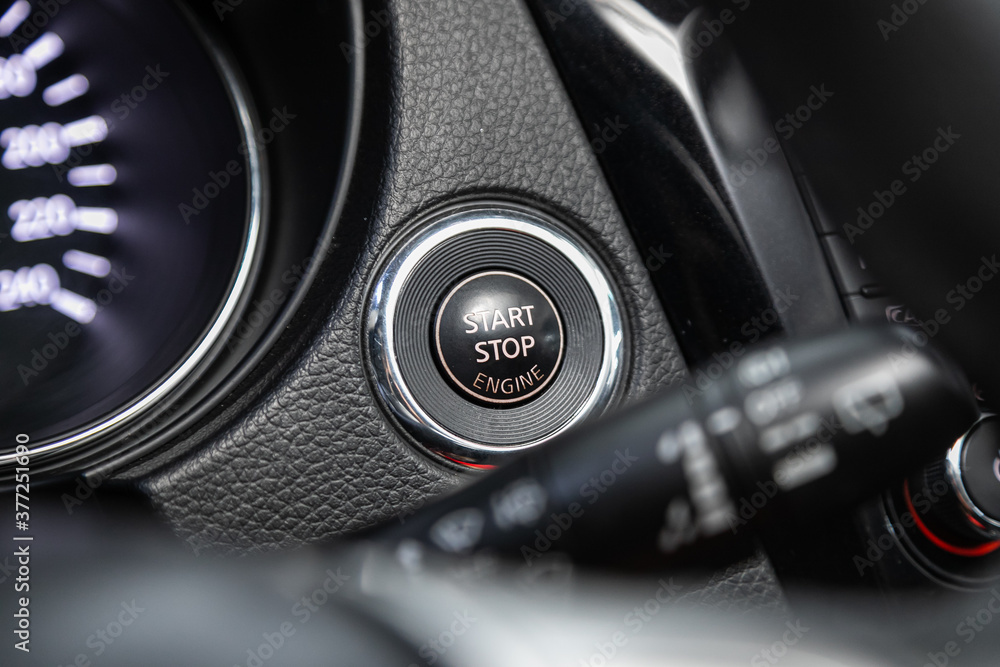 Fototapeta Car dashboard:  black engine start stop button, car interior details. Soft focus..