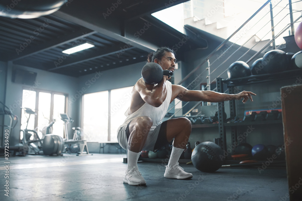 Fototapeta Gym. Man Doing Squats With Kettlebell. Portrait Of Sexy Asian Sportsman Training At Fitness Center. Handsome Guy With Strong, Healthy, Muscular Body. Workout As Lifestyle.