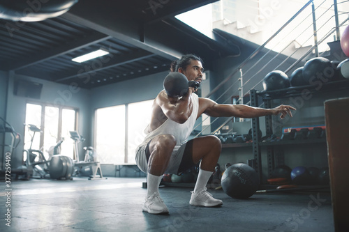 Gym. Man Doing Squats With Kettlebell. Portrait Of Sexy Asian Sportsman Training At Fitness Center. Handsome Guy With Strong, Healthy, Muscular Body. Workout As Lifestyle.