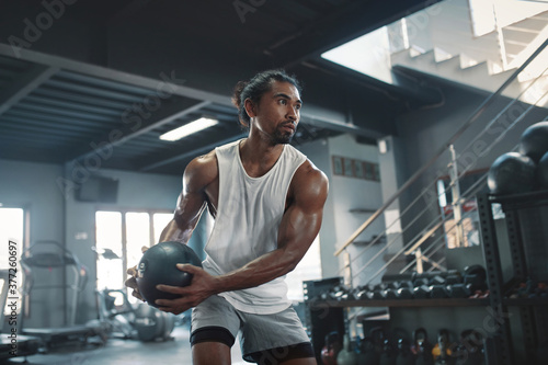 Man On Kettlebell Workout. Sexy Asian Sportsman With Strong, Healthy, Muscular Body Using Heavy Fitness Equipment. Training At Gym For Bodybuilding As Lifestyle.
