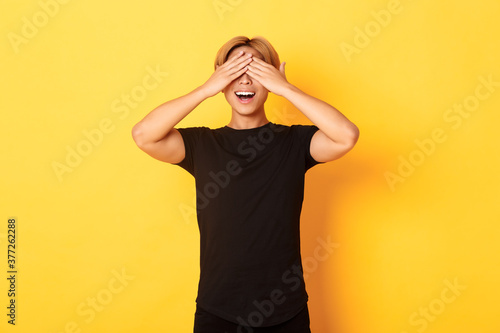 Portrait of amused and excited smiling blond guy shut eyes with palms, waiting f Tapéta, Fotótapéta