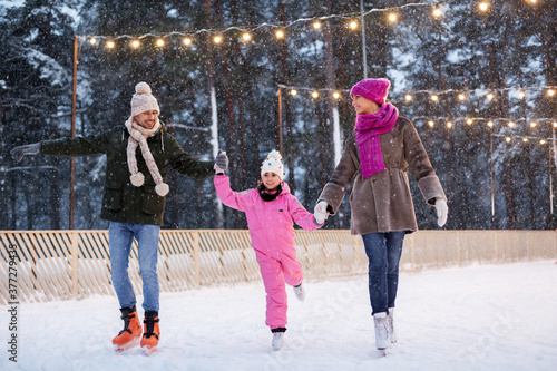 Fototapeta christmas, family and leisure concept - happy mother, father and daughter at out