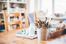 Painting Brushes Of Different Form And Size Stand In Small Aluminium Bucket On Brown Wooden Table With Various Stuff Of Artist At Workshop Close View.