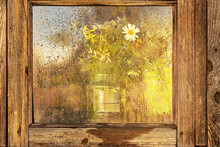 Vase With A Bouquet Of Wild Flowers Through The Wet Window Glass At Sunset. Autumn Season