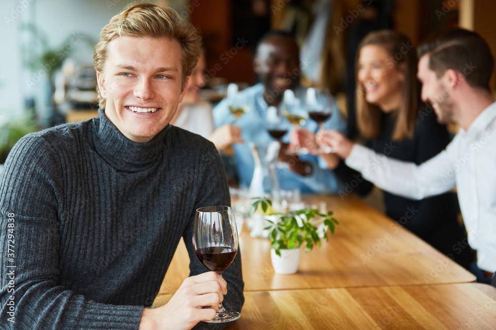 Fototapeta Glücklicher junger Mann mit einem Glas Rotwein