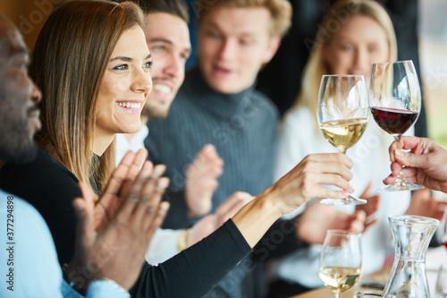 Junge Frau beim Anstoßen mit einem Glas Wein #377294898