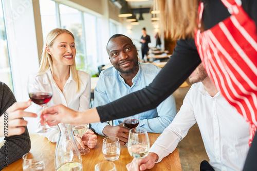 Fotografia Servicekraft als Aushilfe bedient Paar im Restaurant