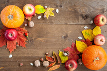 Thanksgiving. Harvest. The Composition Of Autumn Fruits, Vegetables, Nuts And Leaves On A Brown Wooden Background. View From Above. A Place For Text.