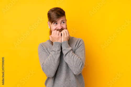 Photo Redhead man with long beard over isolated yellow background nervous and scared p