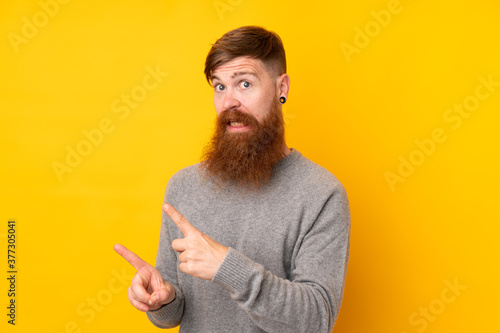 Fototapety, obrazy: Redhead man with long beard over isolated yellow background frightened and pointing to the side