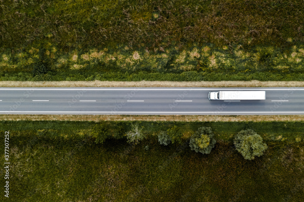 Fototapeta Large freight transporter semi-truck on the road, aerial view