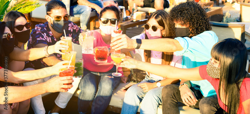Foto Friends drinking cocktail at bar with face masks
