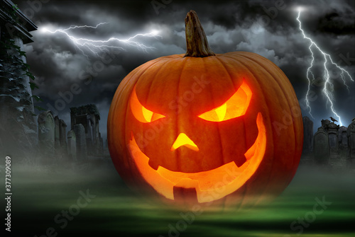 Photo Glowing Jack o Lantern in a dark graveyard with lightning bolts in the night sky