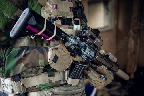Fotografie, Obraz Weapons close-up on a military man standing inside the building and waiting for command