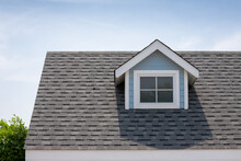 Roof Shingles With Garret House On Top Of The House Among A Lot Of Trees. Dark Asphalt Tiles On The Roof Background