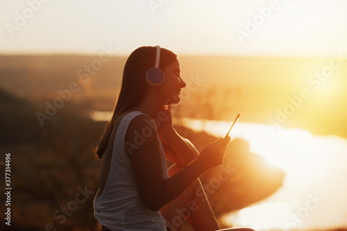 Fotografía Portrait of young tender girl enjoy her weekends at nature and listening to music via headphones