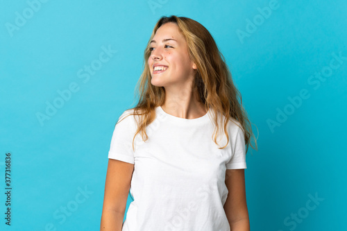 Young blonde woman isolated on blue background looking side Canvas