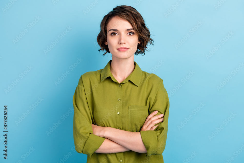 Fototapeta Photo of charming lady short hairstyle calm serious self-assured look confident folded hands camera wear green shirt isolated blue color background
