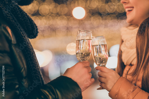 Cropped photo of couple celebrate x-mas christmas newyear clink cheers champagne glass outdoors wear season clothes
